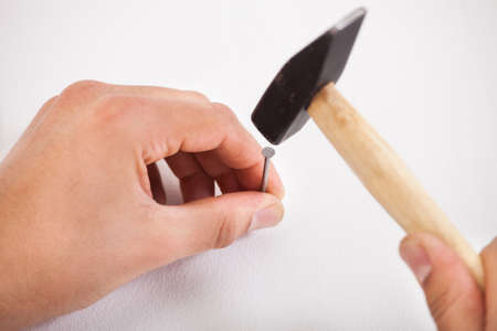Closeup of hands hammering white wall with nail photo