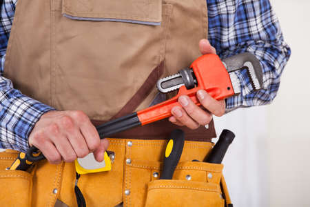 Midsection of male repairman with tool belt holding pipe wrench Stock Photo