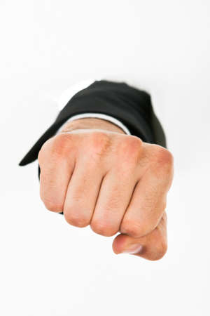 Businessmans hand punching through white paper wall photo