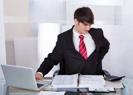 Young businessman suffering from backache at desk in office photo