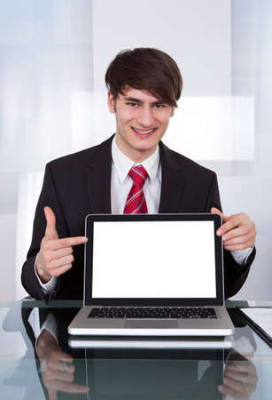 Portrait of confident businessman displaying laptop at desk in office photo
