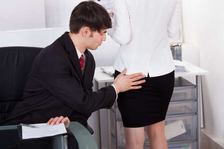 Pervert businessman touching female colleagues buttock in office photo