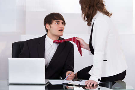 Young businesswoman pulling male colleagues tie while seducing him at desk in office photo