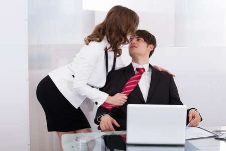 Sensuous secretary seducing boss at desk in office photo