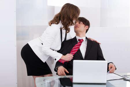 Sensuous secretary seducing boss at desk in office photo
