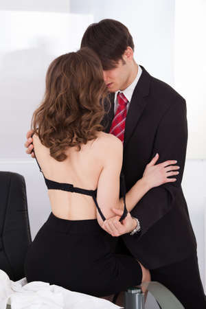 Young businesswoman seducing her boss in the office photo