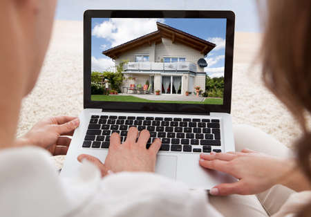 Couple Looking At House On Laptops Screen photo