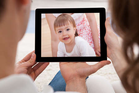 Couple Looking At Tablet Screen With The Image Of Baby photo