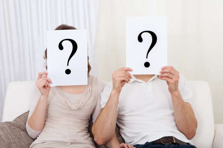 Couple in the living room with question marks in front of their faces photo