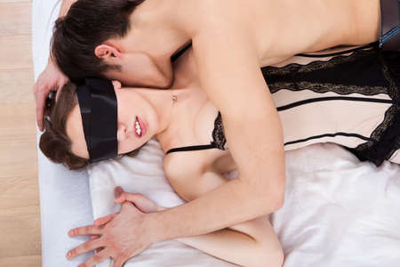 Side view of young man kissing sexy blindfolded woman in bed at home photo