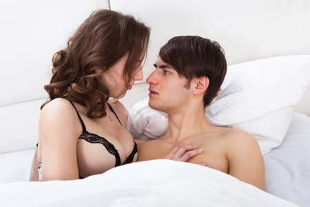 Intimate young couple looking at each other in bed at home photo