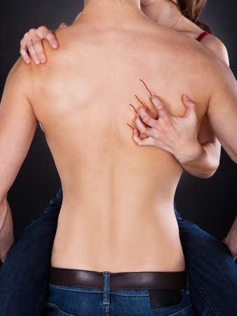 Hand Kratzen wieder mit nacktem Oberk�rper Mannes �ber schwarzem Hintergrund Leidenschaftliche Frau photo