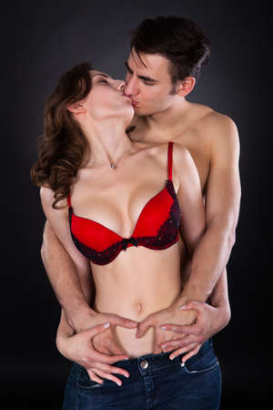 Front view of passionate young couple standing isolated over black background photo
