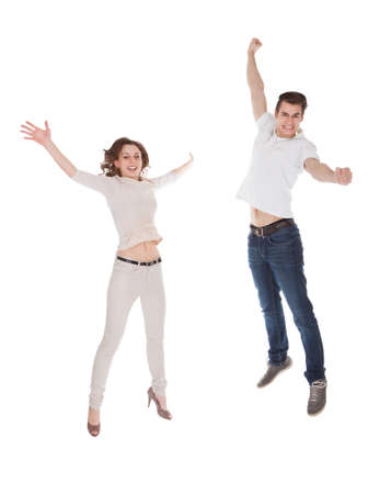 Full length portrait of excited young couple in casuals jumping isolated over white background photo