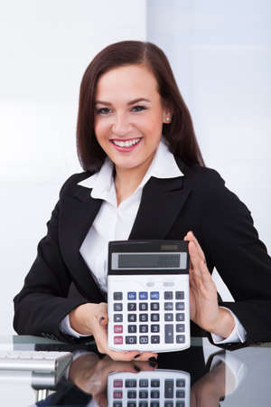 Portrait of happy young businesswoman holding calculator at desk in office photo