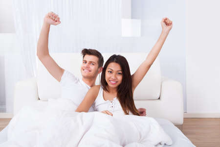 Portrait of happy young couple with arms raised sitting on mattress at home photo