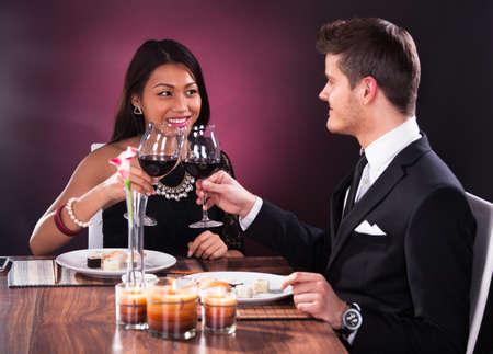 Loving couple looking at each other while toasting wineglasses at restaurant table photo