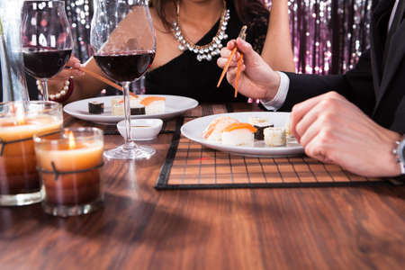 Cropped image of young couple having meal at restaurant table photo