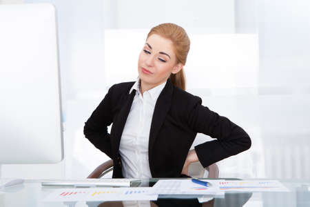 Young Businesswoman Having Back Pain While Sitting At Office Desk photo