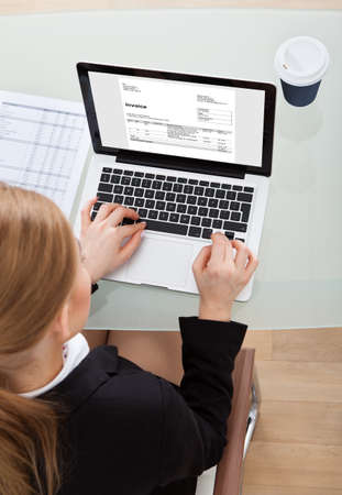 High Angle View Of Businesswoman Using Laptop Preparing Invoice photo