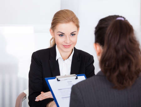 conducting: Businesswoman Conducting An Employment Interview With Young Female Applicant Stock Photo
