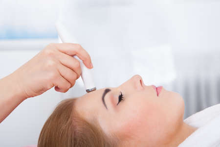 High Angle oog van de vrouw Getting Microdermabrasie Therapy In Spa
