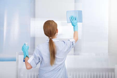 幸せな若いメイド クリーニング ガラス スポンジの肖像画