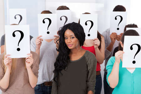 Portrait of confident female college student surrounded by classmates holding question mark signs in classroom photo