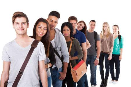 Portret van vertrouwen in de multi-etnische universitaire studenten staan in een rij tegen een witte achtergrond