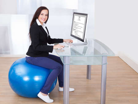 Side view portrait of businesswoman using computer while sitting on pilates ball in office photo