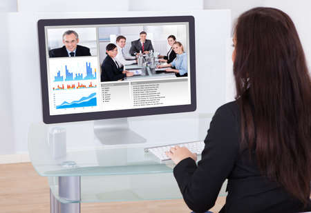 Rear view of businesswoman using having video conference in office Stock Photo