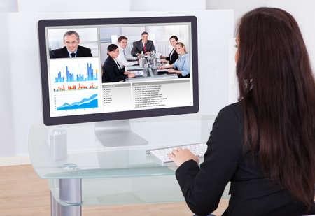 ordinateur bureau: Vue arrière de femme d'affaires à l'aide ayant vidéoconférence dans le bureau