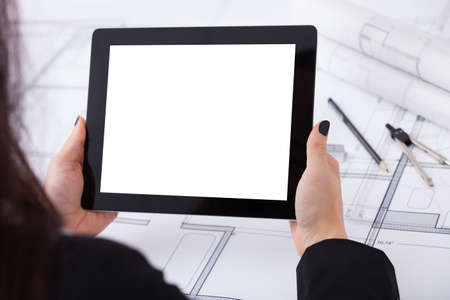 over the shoulder view: Over the shoulder  view of architect woman with digital tablet and blueprint at desk in office Stock Photo