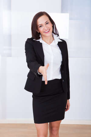 Portrait of happy young businesswoman offering handshake in office photo