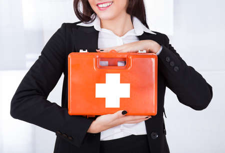 Midsection of young businesswoman holding first aid box in office