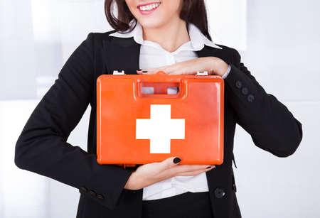 Sección media de la joven empresaria celebración de caja de primeros auxilios en la oficina Foto de archivo