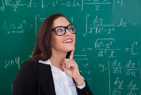one female: Thoughtful young teacher looking at chalkboard in classroom Stock Photo