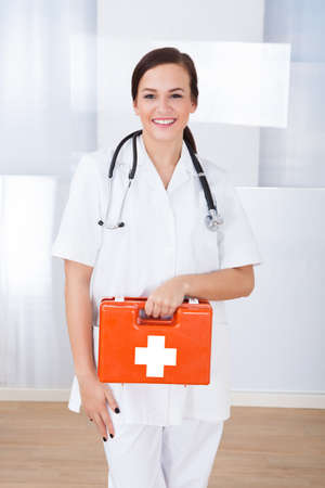 Portrait of happy young female doctor holding first aid box in hospital photo