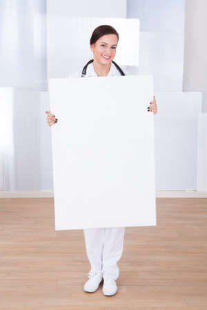 Portrait of happy young female doctor presenting blank billboard in hospital photo