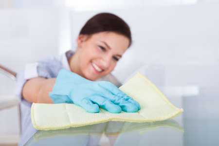 profesionálové: S úsměvem mladá služka čištění skleněný stůl doma Reklamní fotografie