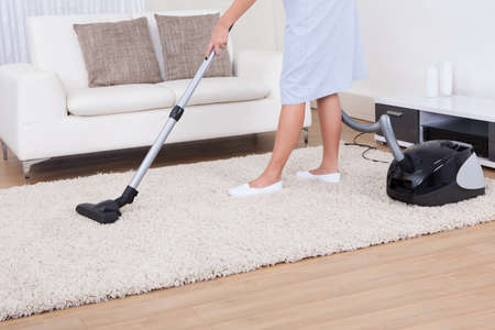 vacuum: Cropped image of young maid cleaning carpet with vacuum cleaner at home Stock Photo