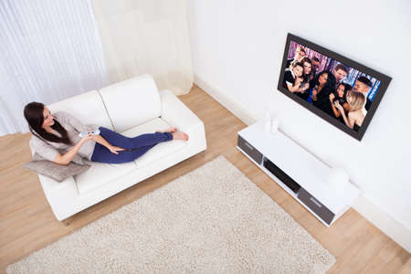 Full length of young woman watching TV while relaxing on sofa at home photo