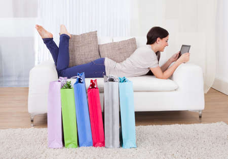 Full length of young woman using digital tablet with shopping bags on floor at home photo
