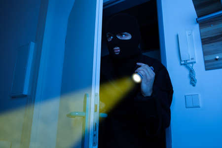 Thief holding flashlight while secretly entering into house photo