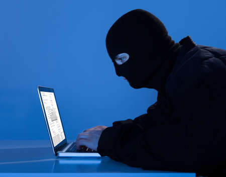 hack: Side view of criminal using laptop to hack data at table