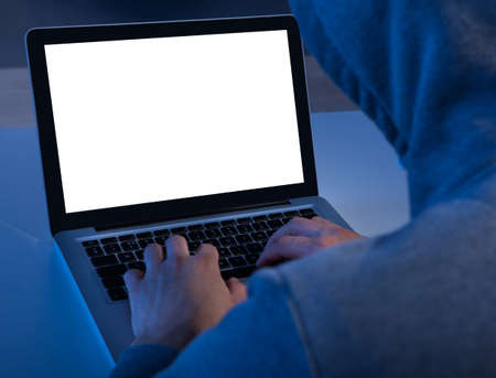 Cropped image of criminal using laptop to steal data at table photo