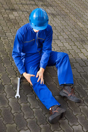 Full length of technician suffering from knee pain while sitting on street photo
