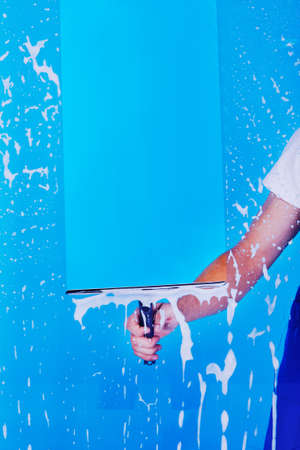 Cropped image male servant cleaning glass with squeegee over blue background Stock Photo
