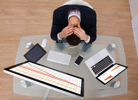 High angle view of frustrated businessman sitting at office desk photo