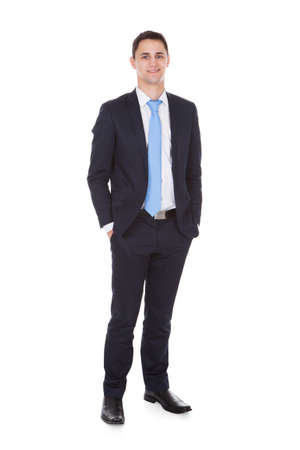 Full length portrait of confident businessman standing with hands in pockets against white background photo